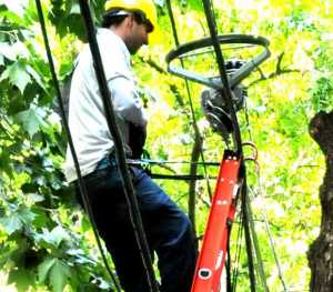 The man is attached to the ladder with a safety strap, but the ladder isn't attached to anything secure.